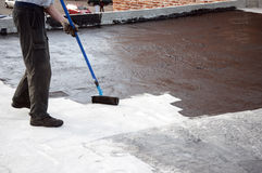 Roofer worker painting bitumen praimer at concrete surface by t. He roller brush,   for waterproofing royalty free stock photos
