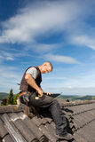 Roofer working on a metal sheet on the rooftop Stock Photography