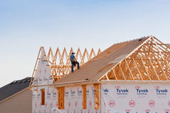 Roofer working on new construction house. Royalty Free Stock Images