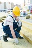 Rooferarbeider die isolatiemateriaal meten stock afbeeldingen