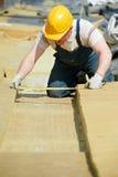 Rooferarbeider die isolatiemateriaal meten royalty-vrije stock afbeeldingen