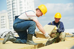 Rooferarbeitskraft, die Dachisoliermaterial installiert Stockbilder