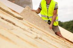 Rooferbyggmästarearbetare som installerar takisoleringsmaterial på nytt hus under konstruktion royaltyfria bilder
