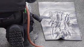 Rooferen som installerar lampglaset genom att använda bitumen, och gas flammar arkivfilmer
