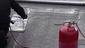 Rooferen som installerar lampglaset genom att använda bitumen, och gas flammar lager videofilmer