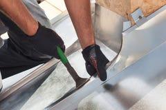 Roofererbauer-Arbeitskraftvollenden, das eine Blechtafel unter Verwendung der speziellen Zangen mit einem großen flachen Griff fa Stockbilder