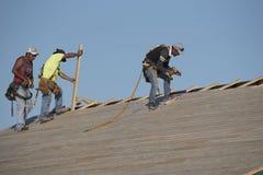 Roofers работая на деревянной крыше Стоковые Фото
