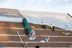 Roofers устанавливая продукты толя CertainTeed стоковое фото