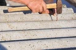 Roofers byter ut den skadade asbesttegelplattan Reparationsasbesttak Spika taksinglar arkivfoto