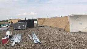 Roofers and a crew repairing a commercial flat roof and materials, tools and supplies stock photo