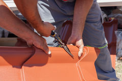 Roofers cut a metal tile using cutting pliers. Roofers cut a metal tile using cutting pliers royalty free stock photos