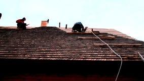 Roofers die aan het dak werken stock video