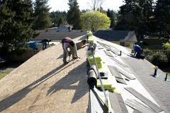 Roofers fixing roofing new roof. Roofers installing new shingles on a house Royalty Free Stock Photos
