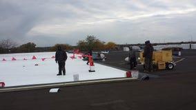 Roofers que executam os trabalhos em curso do telhado, telhado liso comercial com as bandeiras da segurança em Chicago fotografia de stock royalty free
