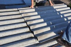 Roofers repair roof and remove asbestos old roof tiles. Roofing construction stock images