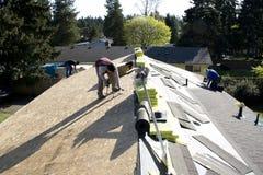 Roofers som fixar taklägga det nya taket Royaltyfria Foton