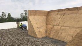 Roofers som reparerar områden av ett kommersiellt plant tak, wood panelgrund av som byggs upp väggen arkivbilder