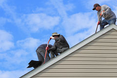 Roofers Work on Roof. Workers Replace Residential Roof on Blue sky background Stock Photography