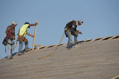 Roofers working on a wooden roof Stock Photos