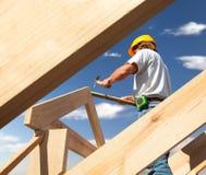 Roofertimmerman die aan dak op bouwwerf werken stock afbeeldingen