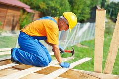 Roofertischler arbeitet an Dach Stockbild