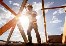 Roofertischler, der an Dach auf Baustelle arbeitet lizenzfreie stockfotos