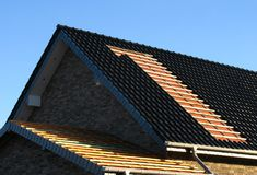 Roofing. Roof cladding with black roofing tiles Stock Images