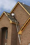 Roofing. Man on new house fixing roof Stock Photos