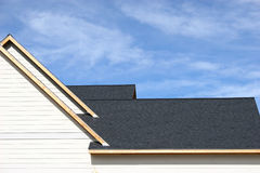 Roofing. Freshly shingled roof on new home with unpainted fascia stock photo