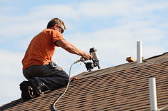 Roofing. Building contractor putting the asphalt roofing on a large commercial apartment building development stock photos