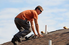 Roofing. Building contractor putting the asphalt roofing on a large commercial apartment building development royalty free stock image