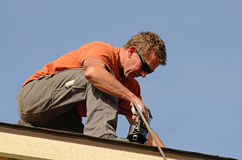 Roofing. Building contractor putting the asphalt roofing on a large commercial apartment building development Stock Image