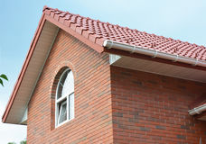 Roofing Construction. Attic brick house roof construction with ceramic clay roof tiles and rain gutter. Royalty Free Stock Photos
