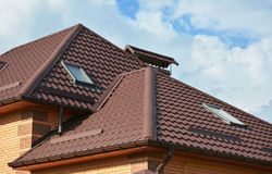 Roofing construction with attic skylights, rain gutter system, roof windows and roof protection from snow Royalty Free Stock Photography