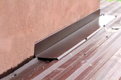 Roofing construction detail close-up. Metal panel on house roof Stock Image