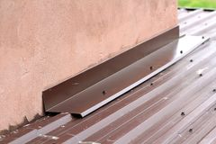 Roofing construction detail close-up. Metal panel on house roof Stock Photos