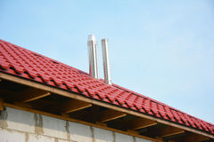 Roofing Construction Exterior. Building new house with metal red roof and steel chimney outdoor. Soffit and Fascia unfinished inst Stock Photo