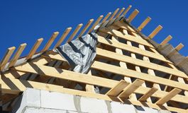 Roofing construction. Installing wooden rafters, logs, eaves, ti. Mber on new house royalty free stock photo