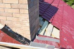 Roofing Construction. Repair roof with  insulation and waterproofing chimney area. Royalty Free Stock Image