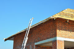Roofing Construction. Roof-trusses. Wooden Roof Frame Unfinished House Construction with metal ladder. Stock Images