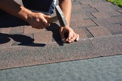 Roofing Construction. Roofer installing asphalt shingles on house construction roof corner with hammer and nails. Photo royalty free stock photo