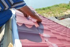 Roofing construction. Roofer installing metal roof sheets on the. Roofing construction. Roofer hands installing metal roof sheets on the house rooftop stock image