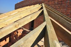 Roofing construction with trusses, wooden rafters, eaves and timber on brick house roof corner. Close up stock image
