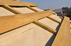 Roofing Construction. Wooden rafters, eaves, waterproofing membrane, logs and timber on house roof corner. Close up stock photos