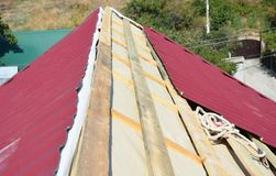 Roofing Contractors Installing House Metal Sheets Roof. Metal Roofing Construction. royalty free stock photography