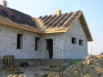 Roofing House Exterior. A roof under construction site with stacks of roof tiles ready to fasten outdoor Stock Photo