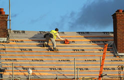 Roofing a house. Workman fixing a roof. Stock Photo