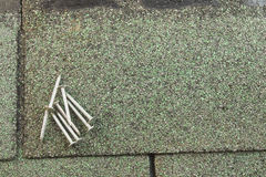 Roofing nails on shingle. Several roofing nails on a green asphalt shingle Stock Image