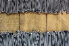Roofing nails on a wooden platform, top view. Royalty Free Stock Image
