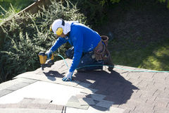 Roofing new roof. A roofer was installing new shingles on a house Royalty Free Stock Image